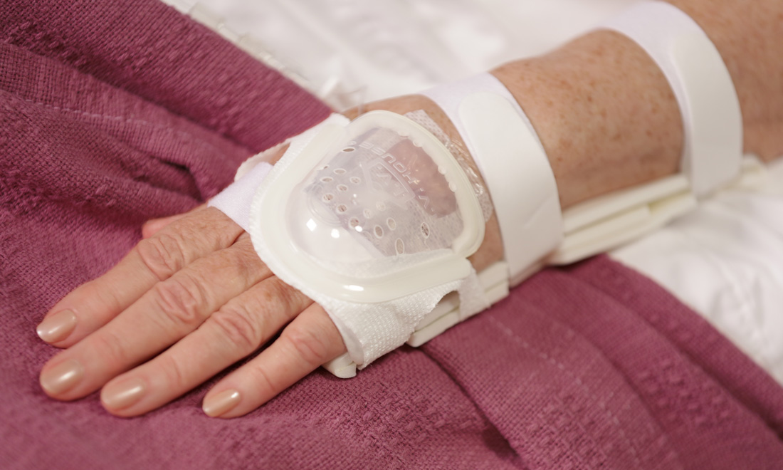 Adult hospital patient with IV protected by I.V. House UltraDome and TLC Splint