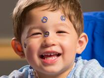 Young boy laughing with puppy stickers on his face